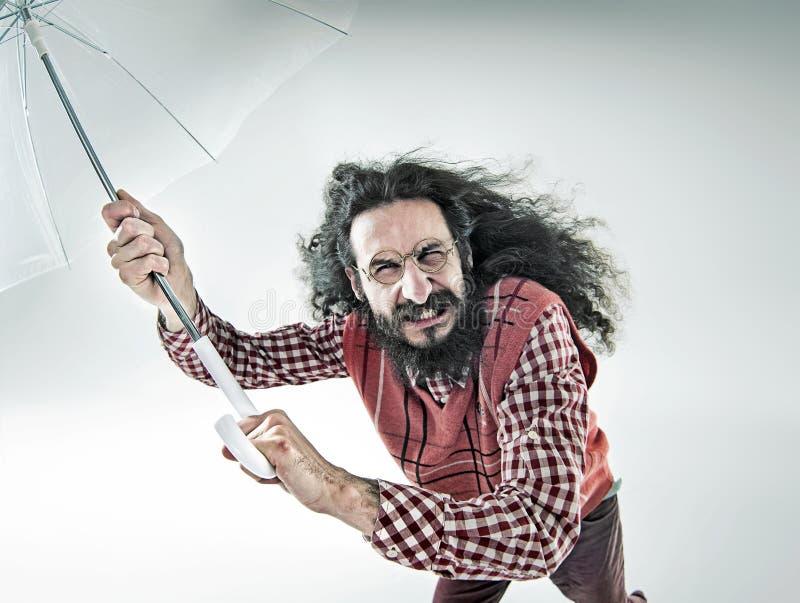Grappig portret van een nerdy kerel die een paraplu houden royalty-vrije stock afbeeldingen