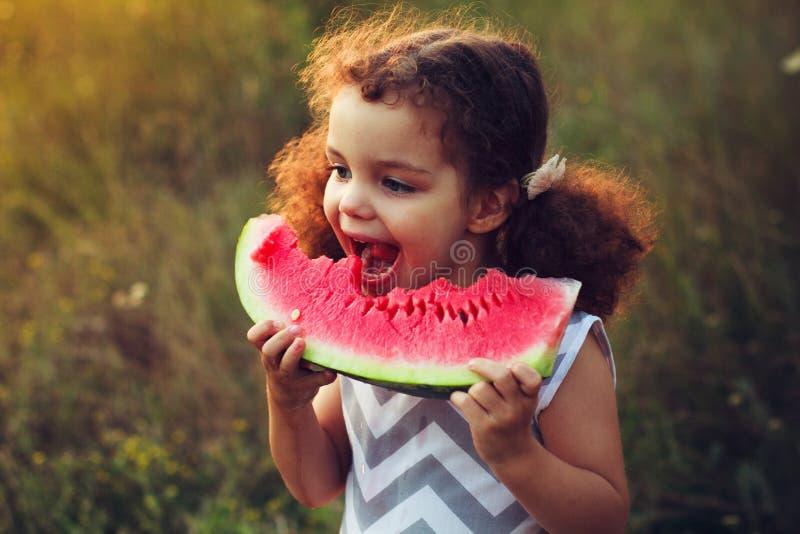 Grappig portret van een ongelooflijk mooi krullend-haired meisje die watermeloen, gezonde fruitsnack, aanbiddelijk peuterkind ete royalty-vrije stock afbeelding
