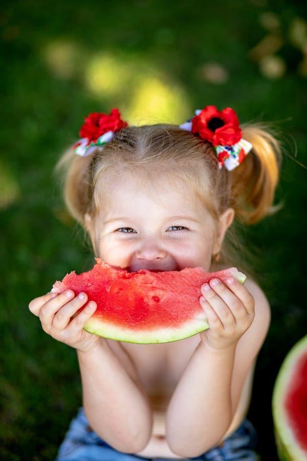 Grappig portret van een ongelooflijk mooi meisje die watermeloen, gezonde fruitsnack, aanbiddelijk peuterkind met het spelen eten stock afbeelding
