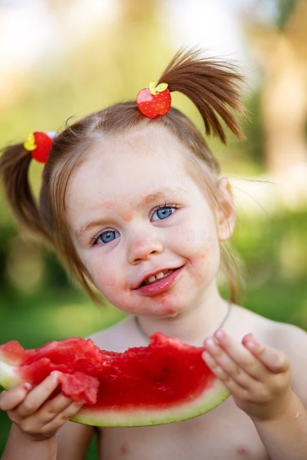 Grappig portret van een ongelooflijk mooi meisje die watermeloen, gezonde fruitsnack, aanbiddelijk peuterkind met het spelen eten royalty-vrije stock afbeelding
