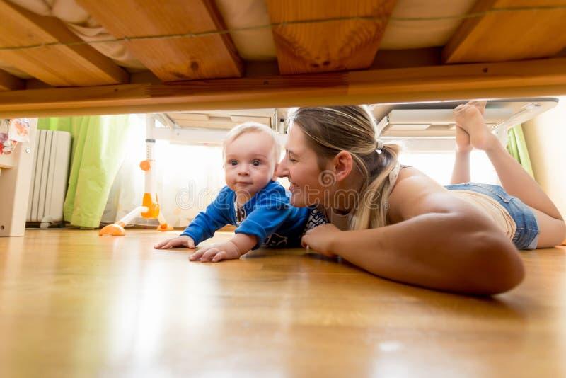 Grappig portret van jonge moeder met babyjongen het liggen op vloer en het kijken onder het bed stock foto