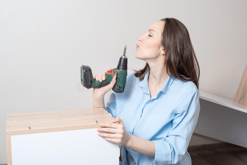 Grappig portret van vrouw met een elektrische schroevedraaier in haar handen die als kanon na succesvol Assemblagemeubilair blaze royalty-vrije stock fotografie