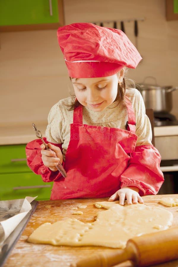 Grappig portret van weinig leuk kindmeisje in deegwaren van de chef-kok de eenvormige kok Concept het eigengemaakte koken stock foto's
