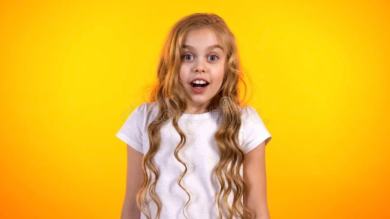 Grappig preteen meisje dat met goed nieuws wordt verrast, kind die op heden, vreugde wachten stock afbeeldingen