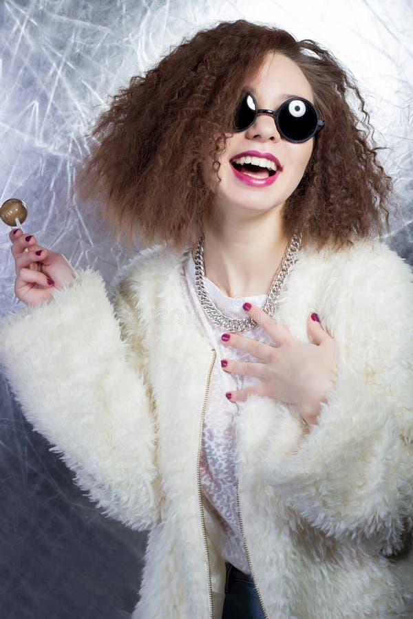 Grappig schadelijk vrolijk meisje die met krullend haar in een witte blouse en jeans in de zon om glazen met suikergoed in studio stock foto's