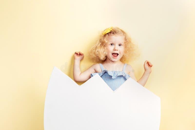 Grappig schenen weinig krullend meisje in de lichtblauwe kleding en gele bloem op haar haar om van het ei op uitgebroed te hebben stock afbeeldingen