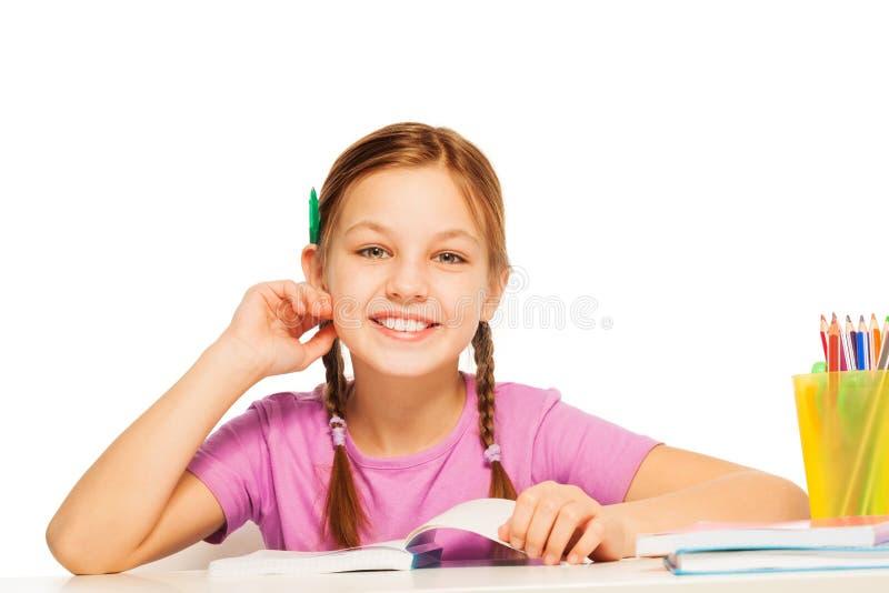 Grappig schoolmeisje met potlood achter haar oor royalty-vrije stock fotografie