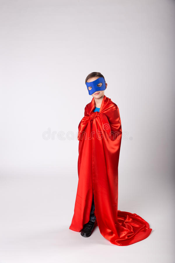 Grappig superherokind in rode kaap en blauw masker stock foto