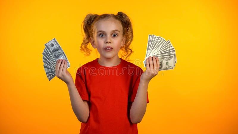 Grappig tienermeisje dat met de winnende bossen van de loterijholding van dollarcontant geld wordt verrast royalty-vrije stock foto's
