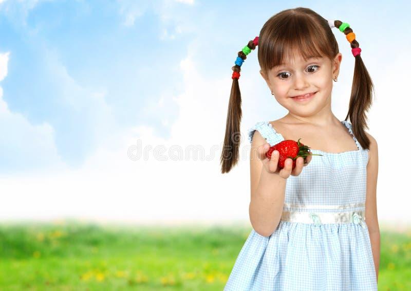Grappig verrast kindmeisje met aardbei royalty-vrije stock foto