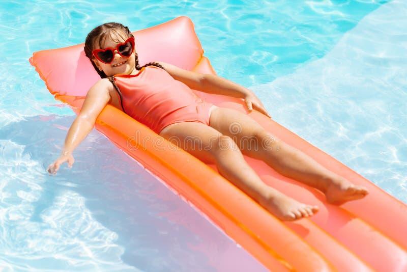 Grappig vrolijk meisje die terwijl het koelen in zwembad glimlachen stock afbeeldingen