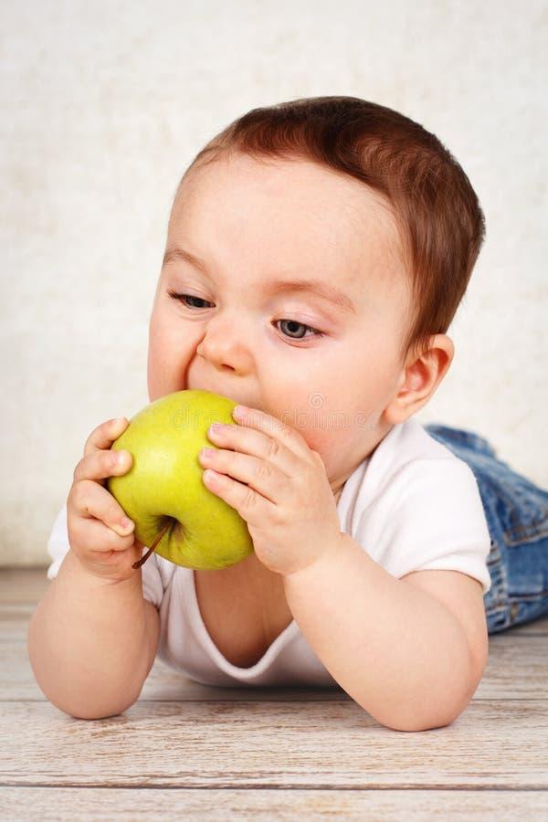 Grappig weinig babyjongen die appel eten stock foto's