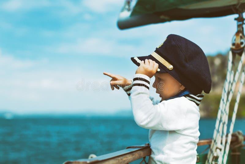 Grappig weinig babykapitein aan boord van varend jacht stock foto