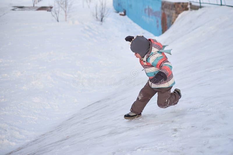 Grappig weinig jong geitjejongen die in kleurrijke kleren in openlucht in de winter op koude sneeuwdagen spelen Gelukkig kind die royalty-vrije stock foto