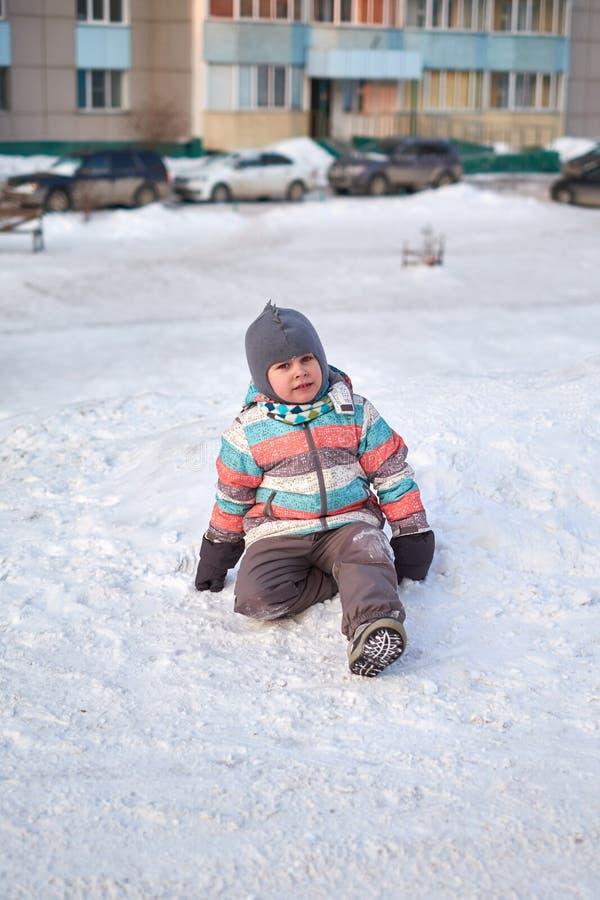 Grappig weinig jong geitjejongen die in kleurrijke kleren in openlucht in de winter op koude sneeuwdagen spelen Gelukkig kind die stock foto's