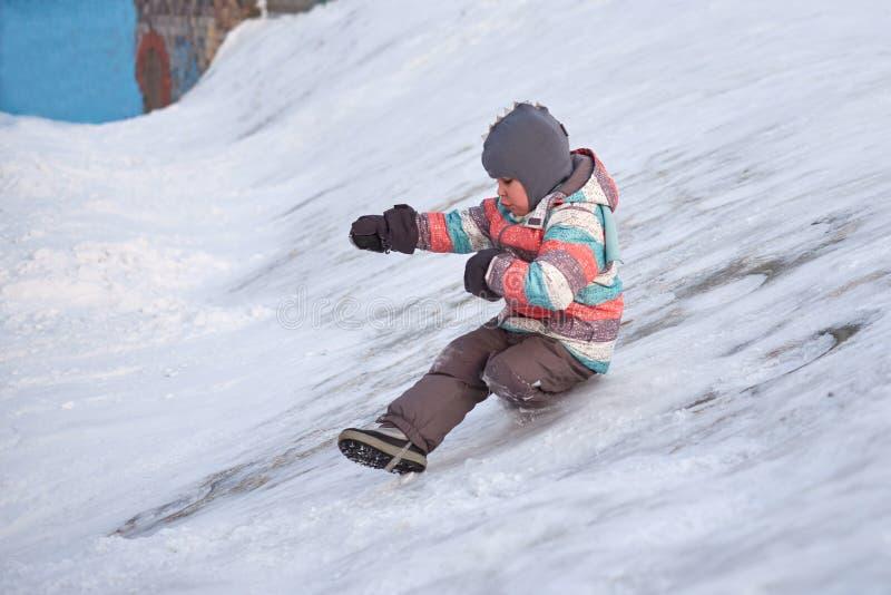 Grappig weinig jong geitjejongen die in kleurrijke kleren in openlucht in de winter op koude sneeuwdagen spelen Gelukkig kind die stock afbeeldingen