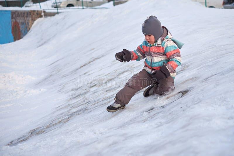 Grappig weinig jong geitjejongen die in kleurrijke kleren in openlucht in de winter op koude sneeuwdagen spelen Gelukkig kind die royalty-vrije stock afbeelding