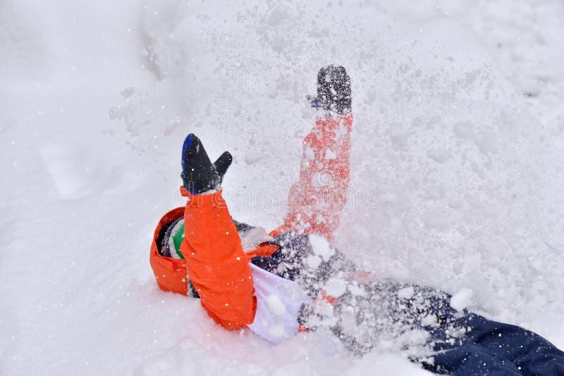 Grappig weinig jong geitjejongen die in kleurrijke kleren in openlucht tijdens sneeuwval in de winter op koude sneeuwdagen spelen stock fotografie