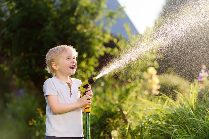 Grappig weinig jongen die met tuinslang spelen in zonnige binnenplaats royalty-vrije stock fotografie