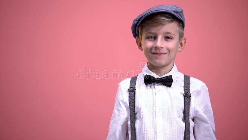 Grappig weinig jongen die in uitstekende kleren op camera tegen roze achtergrond glimlachen royalty-vrije stock fotografie