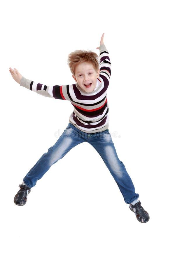 Grappig weinig jongen in gestreepte t-shirtsprongen met haar stock foto's