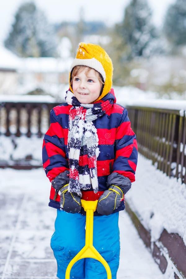 Grappig weinig jongen in kleurrijke kleren gelukkig over sneeuw, in openlucht stock afbeeldingen