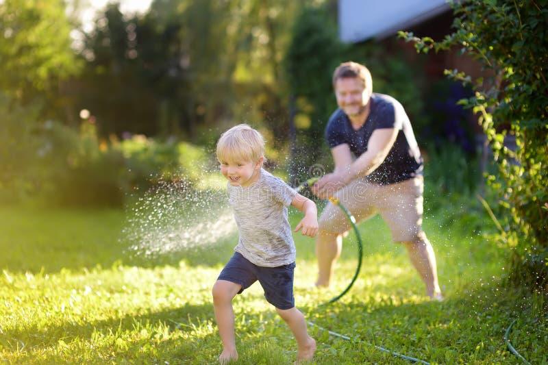 Grappig weinig jongen met zijn vader die met tuinslang spelen in zonnige binnenplaats Kleuterkind die pret met nevel van water he royalty-vrije stock foto