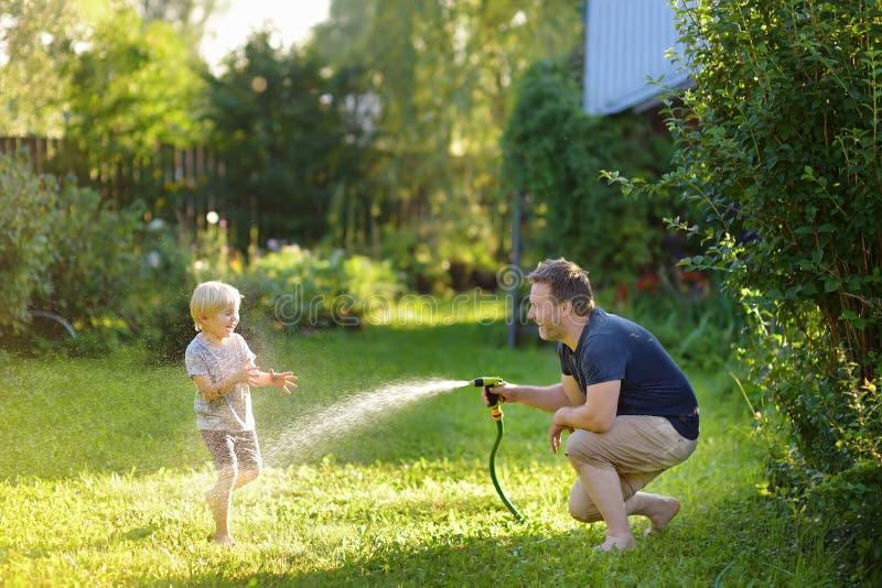 Grappig weinig jongen met zijn vader die met tuinslang spelen in zonnige binnenplaats Kleuterkind die pret met nevel van water he stock fotografie