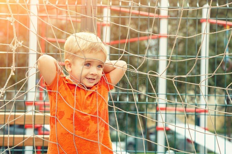 Grappig weinig jongen op speelplaats met een net van voetbalpoort stock fotografie