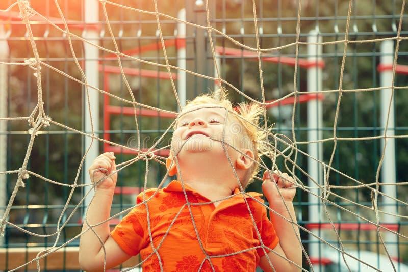 Grappig weinig jongen op speelplaats met een net van voetbalpoort stock afbeelding