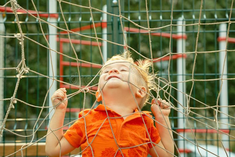 Grappig weinig jongen op speelplaats met net van voetbalpoort speelkind op sportengrond royalty-vrije stock afbeeldingen