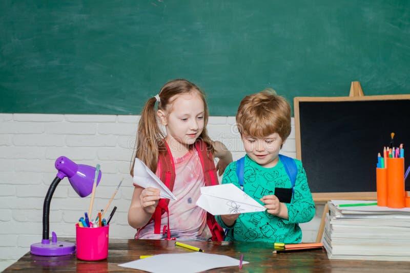 Grappig weinig kind die pret op bordachtergrond hebben Vriendschappelijk kind in klaslokaalspel met document vliegtuig dichtbij stock afbeeldingen