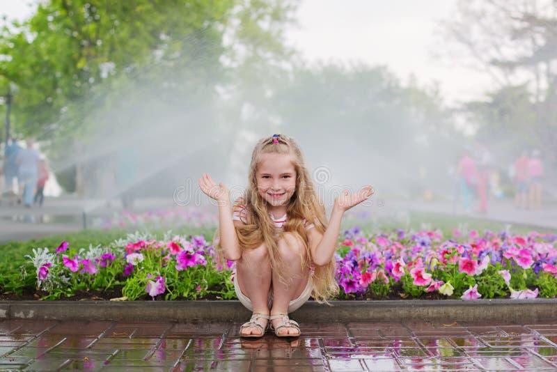 Grappig weinig kleuterkind die pret met nevel van water hebben stock foto