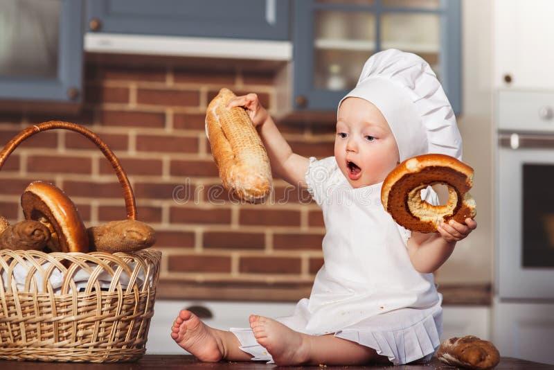 Grappig weinig kok in keuken met bakkerij royalty-vrije stock foto's