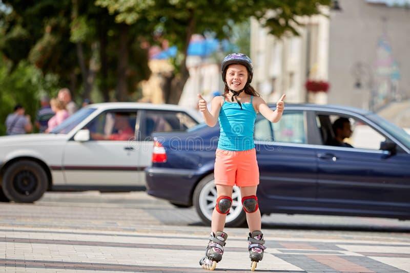 Grappig Weinig mooi meisje op rolschaatsen in helm het berijden in een park stock afbeelding