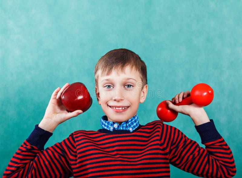 Grappige actieve schooljongen die houdend een appel en een domoor excercising stock foto's