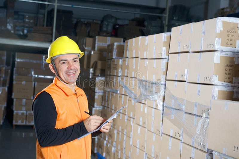 Grappige arbeider in gele helm in pakhuis stock foto's