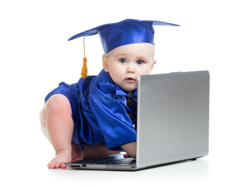 Grappige baby in academicuskleren bij laptop stock foto's