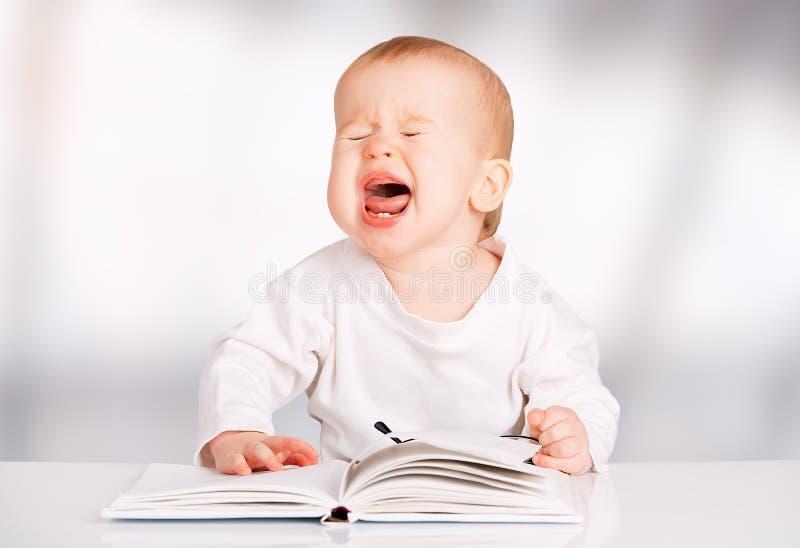 Grappige baby die een boek en schreeuwen lezen stock afbeeldingen