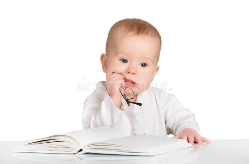 Grappige baby die een boek lezen dat op witte achtergrond wordt geïsoleerd royalty-vrije stock fotografie