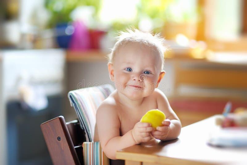 Grappige baby die gezond voedsel eten stock foto's