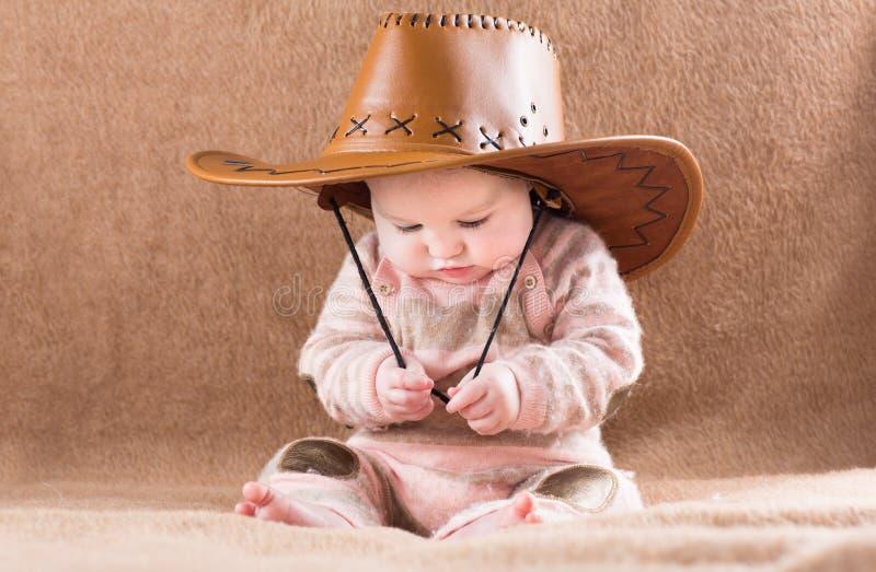Grappige baby in een grote cowboyhoed royalty-vrije stock foto