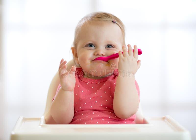 Grappige baby met lepel in haar mond De mooie zitting van het kindmeisje in hoog stoel en wachtenvoedsel Voeding voor jonge geitj stock foto