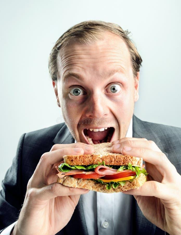 Grappige bedrijfsmens die sandwich eten stock foto