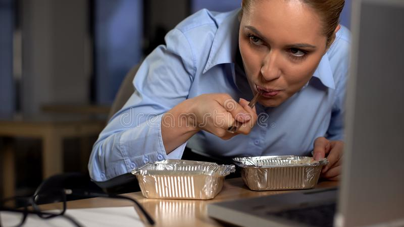 Grappige bedrijfsvrouw die gestolen voedsel eten, die onder computer, gebrek verbergen aan geld stock afbeelding