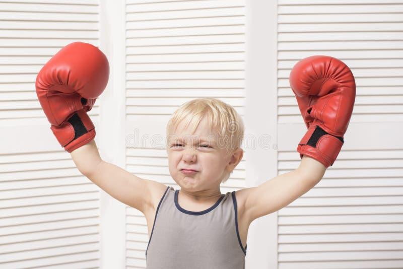 Grappige blonde jongen in rode bokshandschoenen Sportenconcept royalty-vrije stock afbeelding