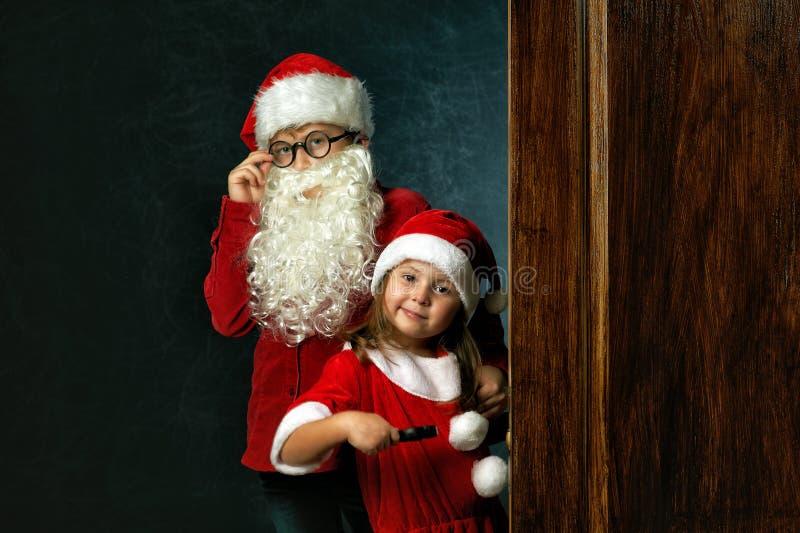 Grappige broer en zuster in Kerstmiskostuums op donkere achtergrond stock foto's