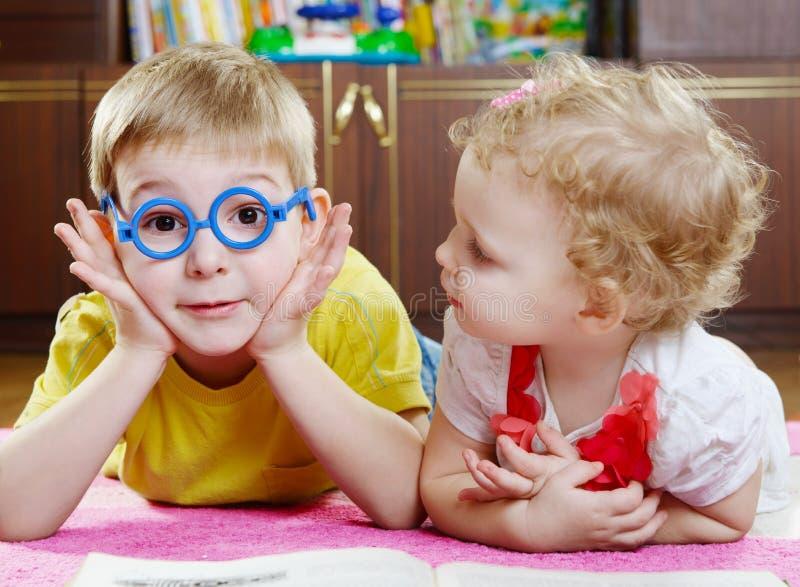 Grappige broer in stuk speelgoed glazen met zuster op vloer stock afbeeldingen