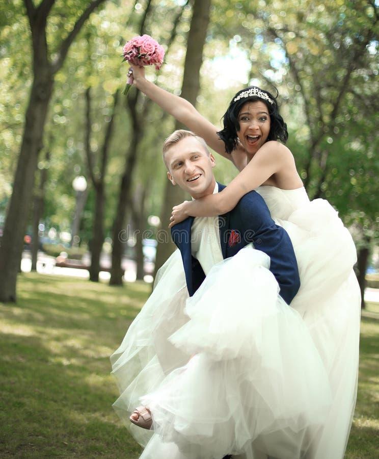 Grappige bruid en bruidegom die pret in het Park hebben stock foto's
