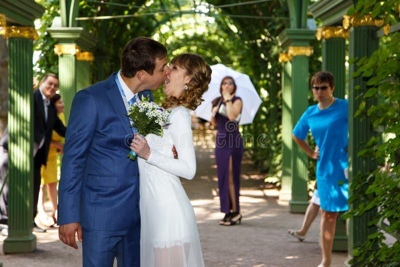 Grappige bruidegom kussende bruid in huwelijkskleding onder de boog stock foto's
